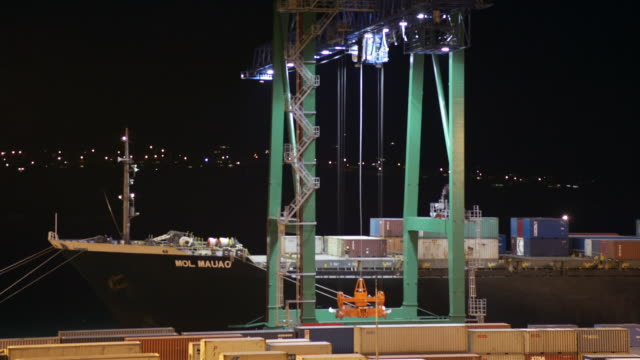 Time lapse crane loading containers onto moored cargo ship in port at night / Port of Lyttelton, New Zealand