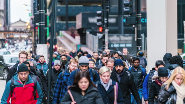 4k time lapse crowd of pedestrians walking on the street in rush hour among modern buildings in chicago, illinois, united states, business and american culture concept - velocità video stock e b–roll