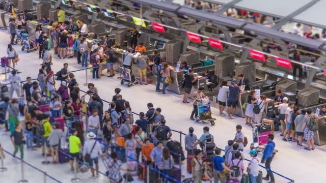 time lapse : crowd of travellers at airport check in zone - security stock videos & royalty-free footage