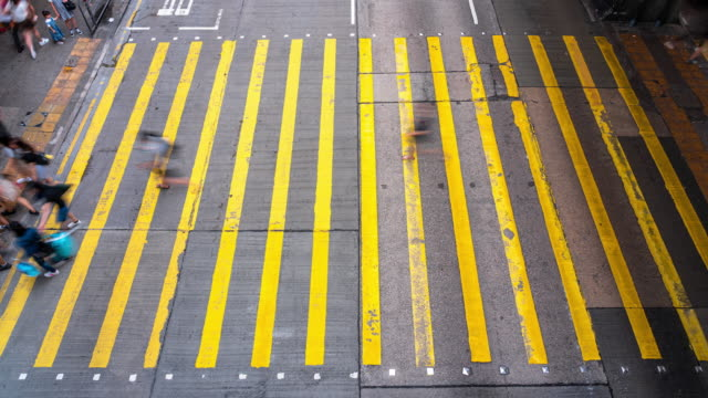 4K Time lapse crowd of Unrecognizable Pedestrians walking and bus riding over the yellow color Zebra Crossing in Mong Kok district at Hong Kong
