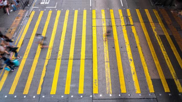4K Zeitraffer Menge von nicht erkennbaren Fußgängern zu Fuß und Bus fahren über die gelbe Farbe Zebra Crossing in Mong Kok Bezirk in Hong Kong