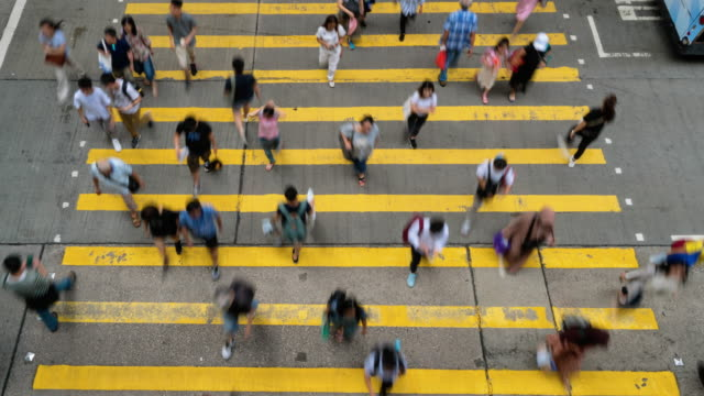 4k time lapse crowd of unrecognizable pedestrians walking and car riding over the yellow color zebra crossing in mong kok district at hong kong - mong kok stock videos and b-roll footage