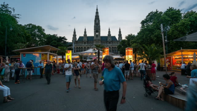 time lapse, crowd waking rathaus at dusk, vienna - austria stock videos and b-roll footage