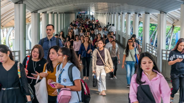 4K Time lapse crowded of anonymous people walking on overpass in elevated train metro system station in rush hour at BTS Chong Nonsi Bangkok, transportation and passenger travel concept