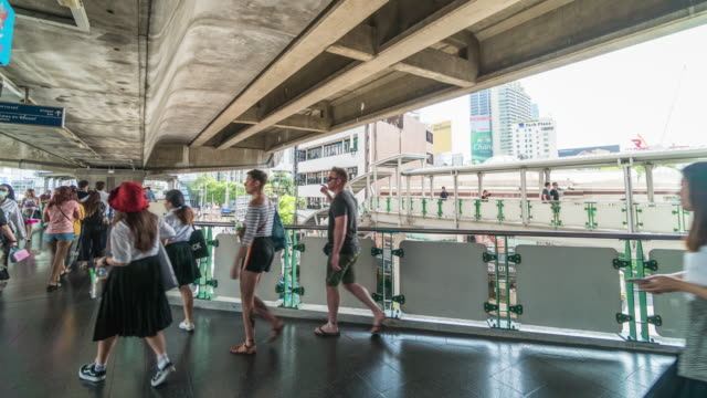 4K Time lapse crowded of people walking on overpass in elevated train metro system station  in rush hour at pressing time in Bangkok, transportation and passenger travel concept