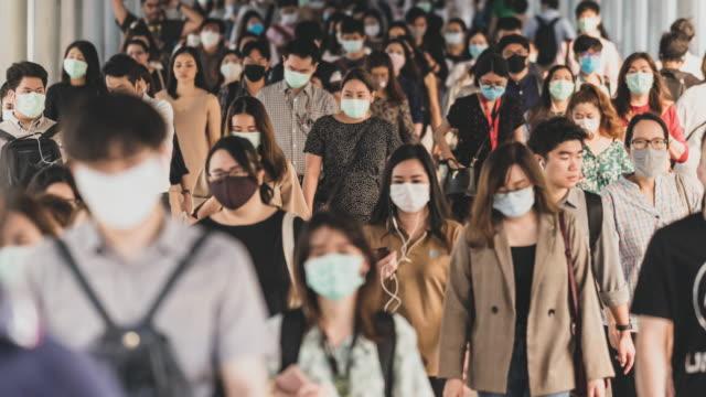 zeitraffer überfüllt von menschen, die eine gesichtsmaske tragen, um coronavirus oder covid19 ausbruch zu verhindern - mundschutz stock-videos und b-roll-filmmaterial
