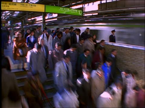 vídeos de stock e filmes b-roll de time lapse crowds getting on + off trains in subway station / shinjuku /tokyo - 1997