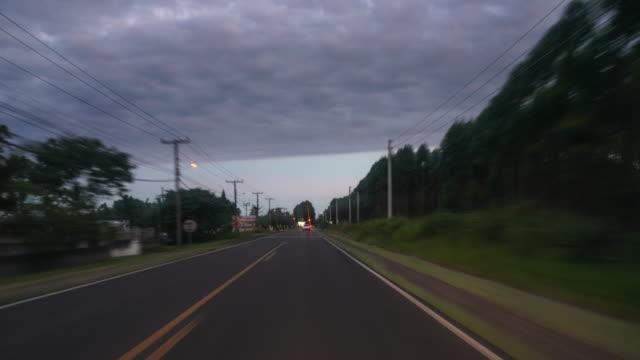 time lapse da chegada de carro a uma cidade ao anoitecer - o anoitecer video stock e b–roll