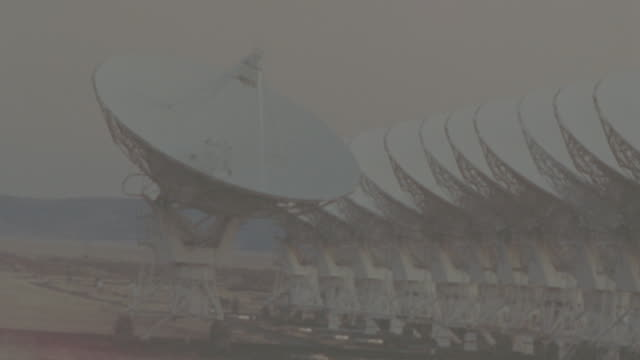 time lapse dawn to day rows of VLA (Very Large Array) radio telescope dishes moving / New Mexico