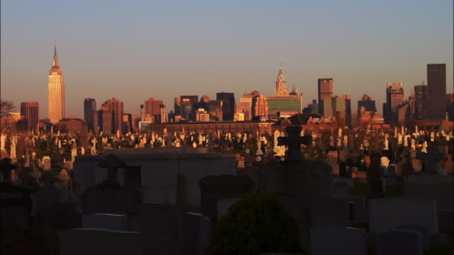 Time lapse dawn to day Wide shot Calvary Cemetery with Manhattan skyline in background / Woodside, Queens, New York