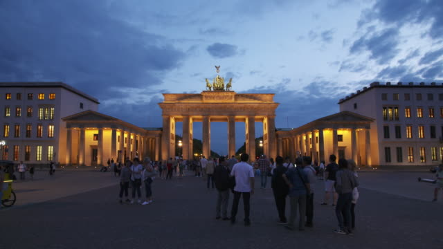Time Lapse day to night. Brandenburger Tor illuminated with pedestrians and tourist. Berlin, Germany, Europe.