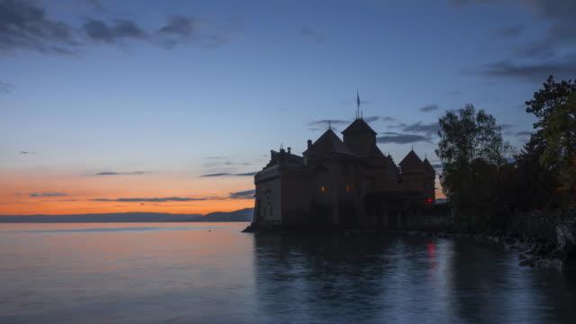 Time Lapse day to night. Chateau de Chillon (Chillon Castle) on the shore of Lake Geneva, sunset.