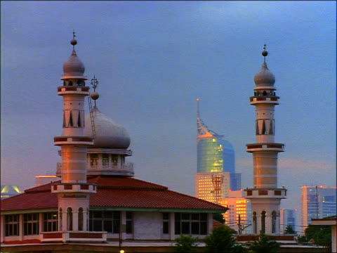 time lapse day to night mosque-like building + skyscraper in background / Jakarta, Java, Indonesia