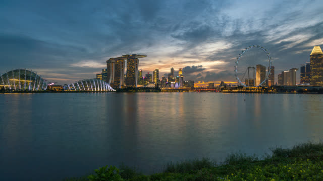 Time lapse day to night scene of Singapore business district downtown at sunset