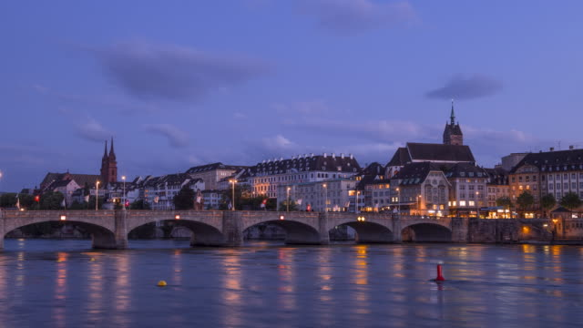 time lapse day to night. the medieval mittlere rheinbrücke (a stone bridge over river rhine) and church martinskirche with view to skyline of basel at. - 夜遊び点の映像素材/bロール