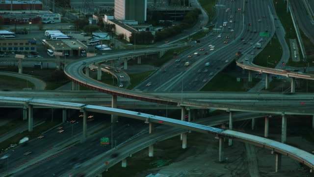 Time lapse day to night, traffic blurs racing around a complex interstate system of overpasses, highways and raised exit ramps.
