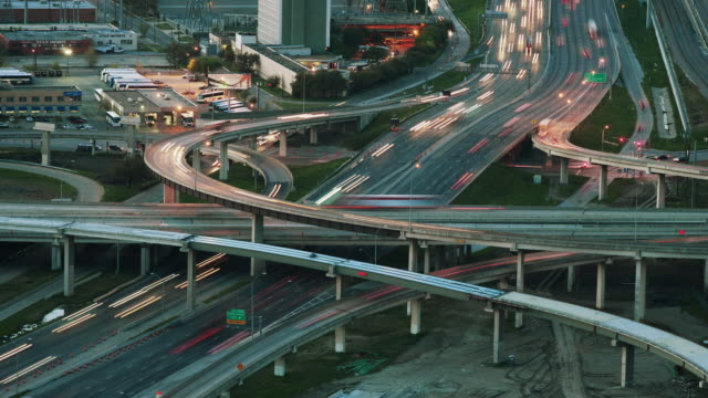 stockvideo's en b-roll-footage met time lapse day to night, traffic blurs racing around a complex interstate system of overpasses, highways and raised exit ramps. - tweebaansweg