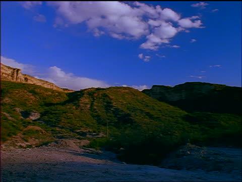 time lapse pan desert mountains + red convertible mustang in foreground / arizona - mustang convertible stock videos & royalty-free footage