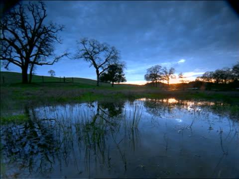 vídeos de stock, filmes e b-roll de time lapse dolly shot clouds + sunset over pond in countryside / sierra nevada foothills near san francsico - céu romântico