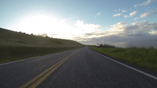 time lapse: driving along a scenic coastal road and lush fields - empty road stock videos and b-roll footage