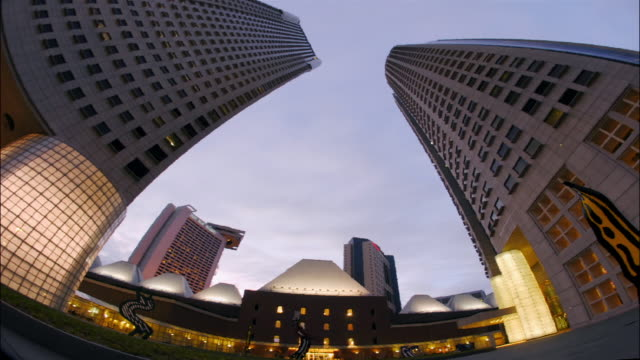 time lapse dusk to night low angle fisheye view of skyscrapers in suntec city / lights turning on / singapore - dusk to night stock videos & royalty-free footage