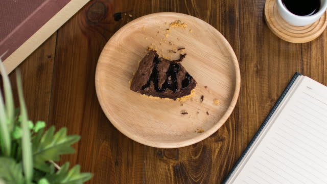 Time Lapse : Eating brownie chocolate cake on wooden dish and wooden table