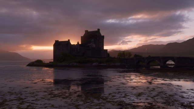 time lapse. eilean donan castle reflecting in loch duich at sunset, scottish highlands. eilean donan castle, dornie, loch duich, scottish highlands, scotland, uk. - dornie stock videos & royalty-free footage