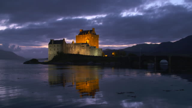 time lapse. eilean donan castle reflecting in loch duich, scottish highlands. eilean donan castle, dornie, loch duich, scottish highlands, scotland, uk. - dornie stock videos & royalty-free footage