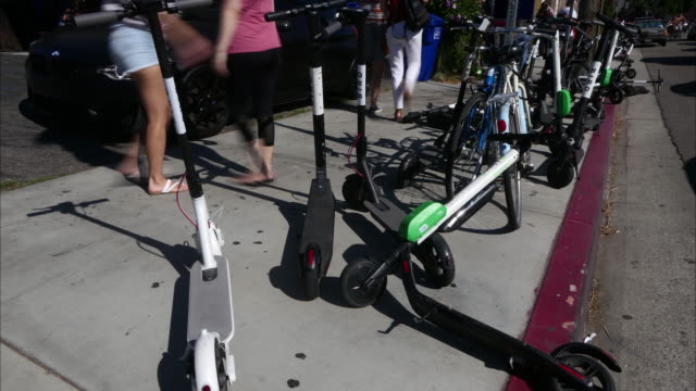 Time lapse electric bird lime scooters massive cluttered sidewalk