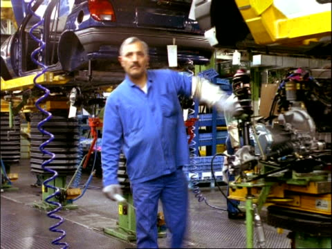 archival time lapse - cu engine and front springs being put into cars, car assembly line, dagenham - continuity stock videos and b-roll footage