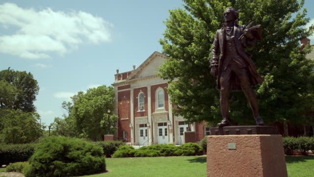 time lapse exterior of collegiate auditorium building with bronze statue of thomas jefferson, blue sky and clouds at wichita state univeristy - wichita stock-videos und b-roll-filmmaterial
