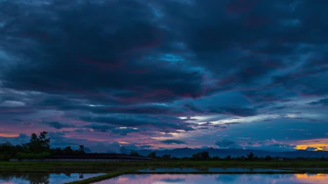 vidéos et rushes de 4k time-lapse: champ et belle réflexion lever du soleil et de l'eau sur étang matin - pluie