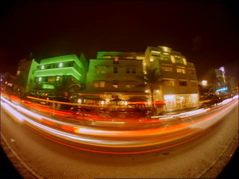 time lapse fisheye traffic + people with art deco buildings on city street at night / miami beach, miami - アールデコ点の映像素材/bロール
