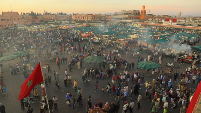 time lapse footage from elevated viewpoint of the bustle main square of jemaa el fna in marrakech city during sunset with people walking in every direction during travel vacations in morocco. - souk stock videos & royalty-free footage