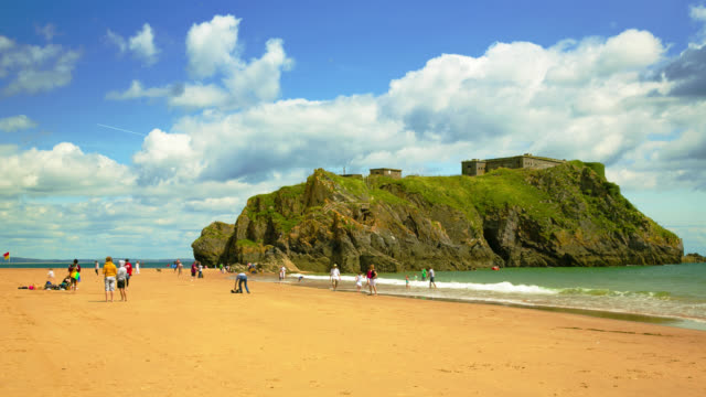 vídeos de stock, filmes e b-roll de time lapse footage of holidaymakers castle beach and st catherine's island in tenby at low tide, south wales. - vazante