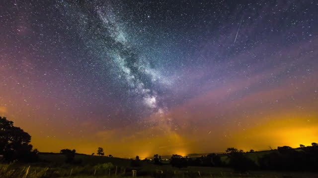 time lapse footage of milky way galaxy rising over welsh rural landscape at welshpool. - stern weltall stock-videos und b-roll-filmmaterial