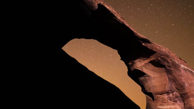 vídeos de stock e filmes b-roll de time lapse footage of natural stone arches of arches national park light painted with a starry night sky overhead, edited with parallax software to... - arco natural