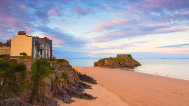 vídeos de stock, filmes e b-roll de time lapse footage of sunset over castle beach and st catherine's island in tenby, south wales at low tide. - vazante