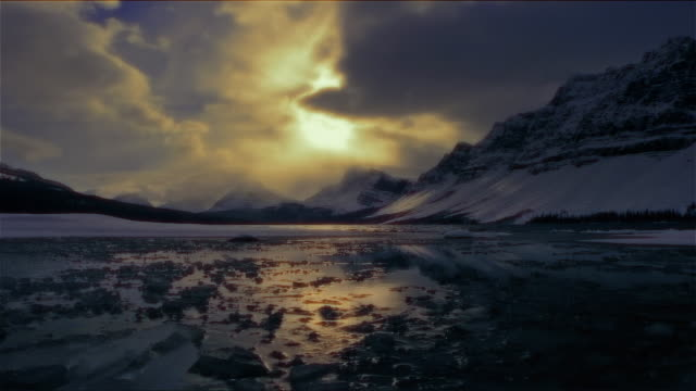 time lapse frozen body of water at night with snow-covered mountain along banks - frozen water stock videos & royalty-free footage