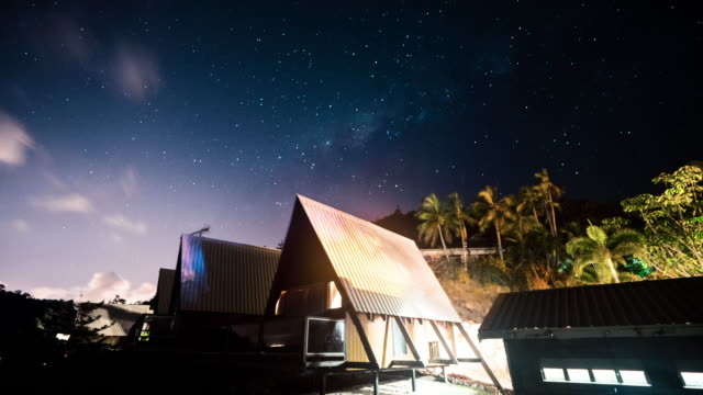 time lapse: gorgeous sky of stars and clouds moving over small hut, palm trees, magnetic island, australia - hut stock videos & royalty-free footage
