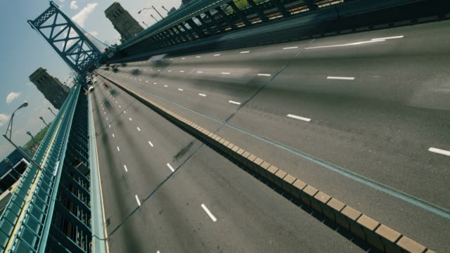 Time lapse, graphic dutch angle, traffic races under camera on the Ben Franklin Bridge.