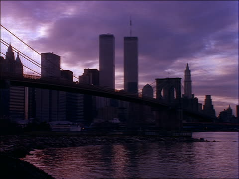 time lapse grey clouds over Brooklyn Bridge + lower Manhattan skyline / day to night