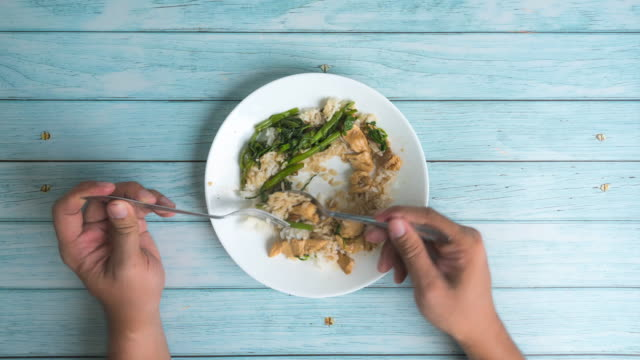time lapse hand of people eating meal with rice, vegetable, chicken on blue wooden table in restaurant - wood plate stock videos & royalty-free footage