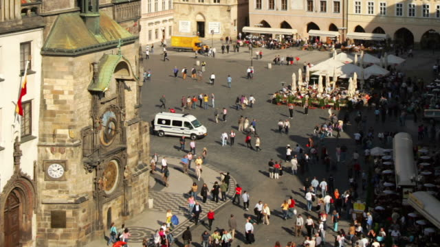 Time lapse high angle crowd in Old Town Square / zoom out Church of Our Lady before Tyn/ astronomical clock in foreground/ Prague