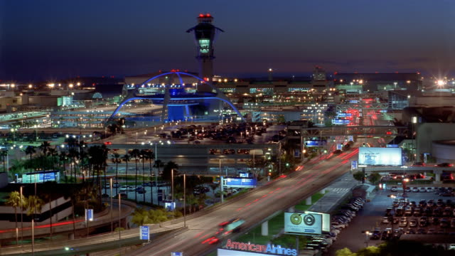 Time lapse high angle long shot illuminated Theme Building, control tower and traffic at LAX at night / Los Angeles
