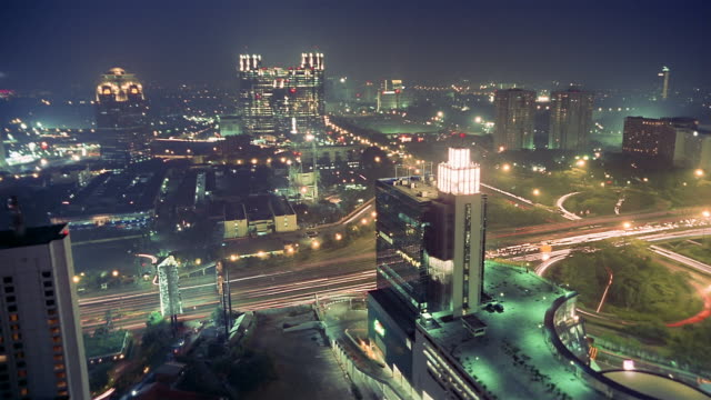 time lapse high angle long shot semanggi highway traffic and skyscrapers at night / pan to cloverleaf / jakarta - two lane highway stock videos & royalty-free footage