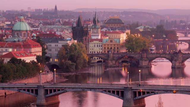 Time lapse high angle long shot view of Charles Bridge and Manesuv Bridge over Vltava at twilight / Prague, Czech Republic