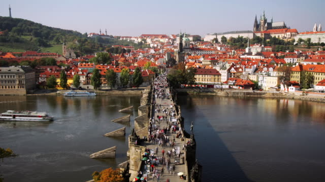 Time lapse high angle long shot view of Charles Bridge over Vltava / Strahov Monastery and Hradcany Castle in background / Prague