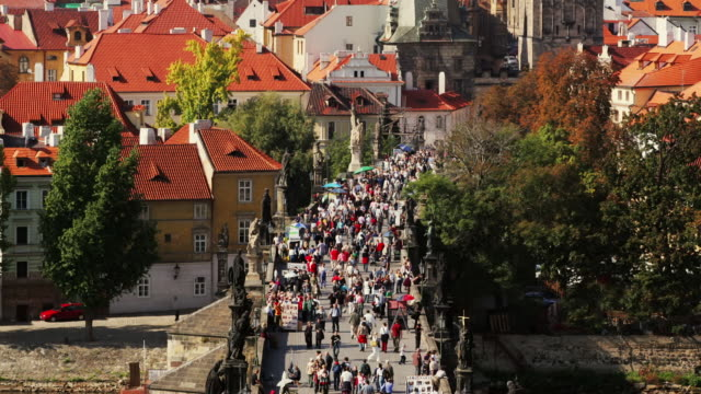 time lapse high angle long shot view of people crossing charles bridge and statues on bridge / prague, czech republic - charles bridge stock videos & royalty-free footage