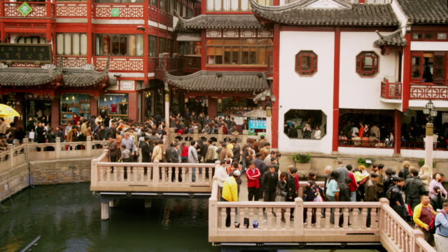 time lapse high angle medium shot tourists crossing nine-turn zig-zag bridge at yuyuan bazaar / shanghai - zigzag stock videos & royalty-free footage